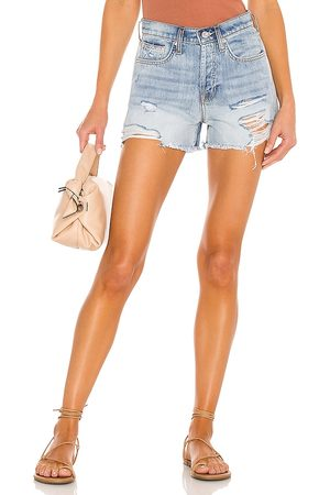 7 for all Mankind Monroe Cut Off Short in - Blue. Size 23 (also in 24, 25, 26, 27, 28, 29, 30, 31, 32).