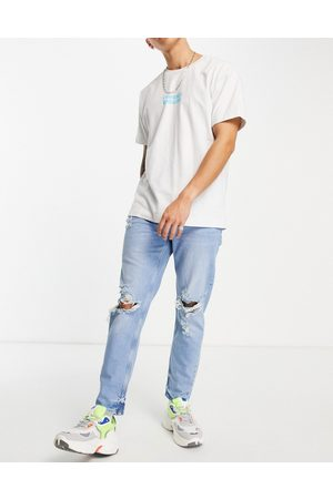 ASOS Tapered carrot jeans in light wash blue with knee rips