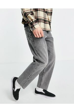 ASOS Relaxed tapered jeans in washed black with raw hem