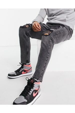 ASOS Tapered carrot jeans in washed black with heavy rips