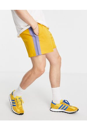 ASOS Homem Calções - Oversized jersey shorts with pin tucks & side tape in mustard yellow