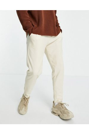 ASOS DESIGN Co-ord waffle tapered joggers in cream with fixed hem-Neutral