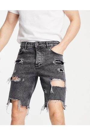 ASOS Slim denim shorts in washed black with heavy rips and raw hem