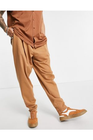 ASOS DESIGN Organic oversized wide leg joggers with pressed pleat in brown