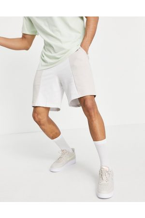 ASOS Unrvlld Supply ASOS Unrvlld Spply co-ord shorts with cut and sew detailing and logo print-Neutral
