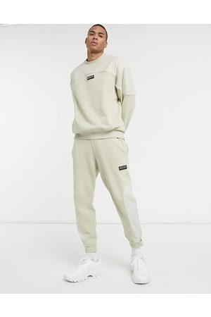 ASOS Unrvlld Supply ASOS Unrvlld Spply co-ord tapered joggers in beige with nylon colour block panels-Neutral