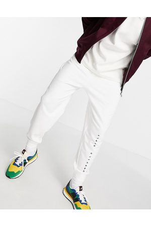 ASOS Unrvlld Supply Homem Joggers - ASOS Unrvlld Spply relaxed joggers with logo print in white