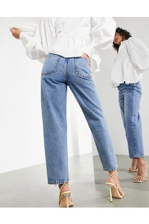 ASOS EDITION Tapered jean with twisted seam in mid wash-Blue