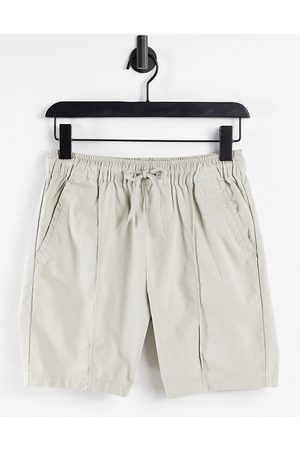 ASOS DESIGN Slim chino shorts with pin tuck and elasticated waist in beige-Neutral