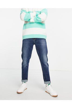 ASOS Homem Tapered - Organic cotton blend tapered jeans in dark wash blue