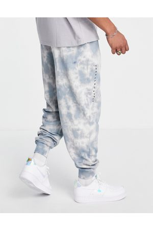 ASOS Unrvlld Spply Co-ord relaxed joggers with all over wash & logo print in blue