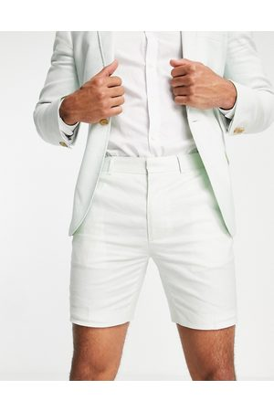 ASOS Homem Calções - Super skinny suit shorts in pastel green cotton linen