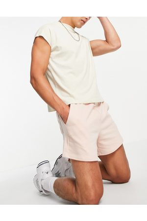 ASOS DESIGN Oversized jersey shorts in shorter length in pink