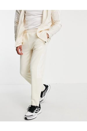 adidas performance Adidas Training joggers with white three stripes in cream