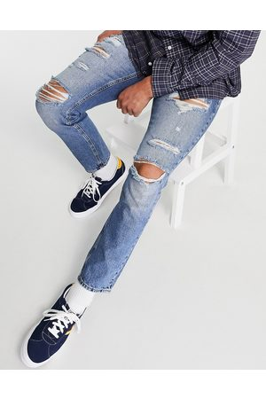 ASOS DESIGN Slim jeans in mid wash blue with heavy rips