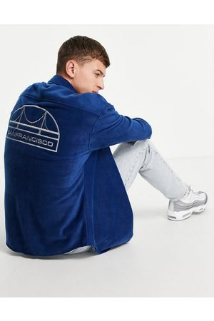 ASOS Homem Casual - 90s oversized collegiate shirt in polar fleece with city back embroidery-Navy