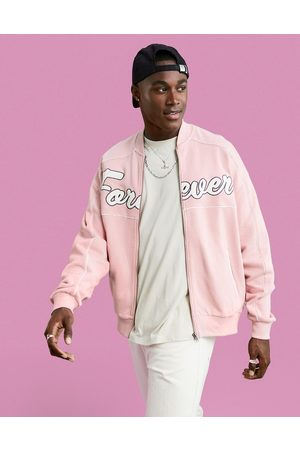 ASOS DESIGN Oversized jersey bomber jacket in pink with large text applique