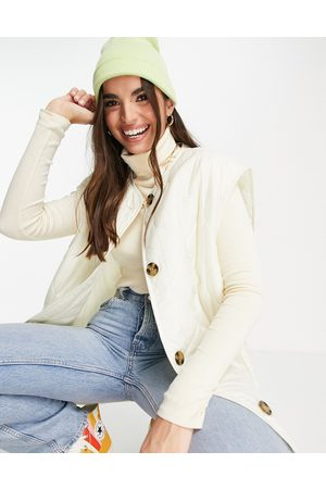 ASOS Quilted collarless gilet in cream-Black