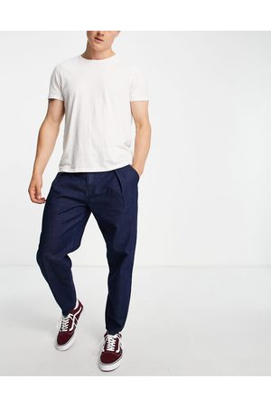 ASOS Homem Tapered - Relaxed tapered pleated jeans in dark blue