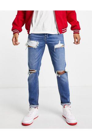 ASOS Homem Slim - Stretch slim jeans in dark wash blue with heavy rips