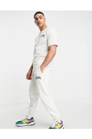 New Balance Collegiate joggers in off white and green
