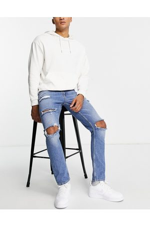 ASOS Homem Slim - Stretch slim jeans in mid wash blue with heavy rips